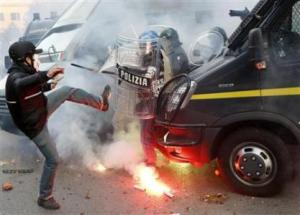 A protester clashes with a Guardia di Finanza policeman in front of the Ministry of Finance building in downtown Rome